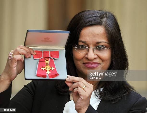 Professor Mona Siddiqui holds her Officer of the British Empire medal, after it was presented to her by the Prince of Wales, during an Investiture...