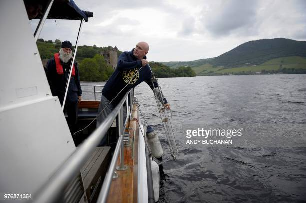 Professor Neil Gemmell takes samples on his boat as he conducts research into the DNA present in the waters of Loch Ness in the Scottish Highlands...