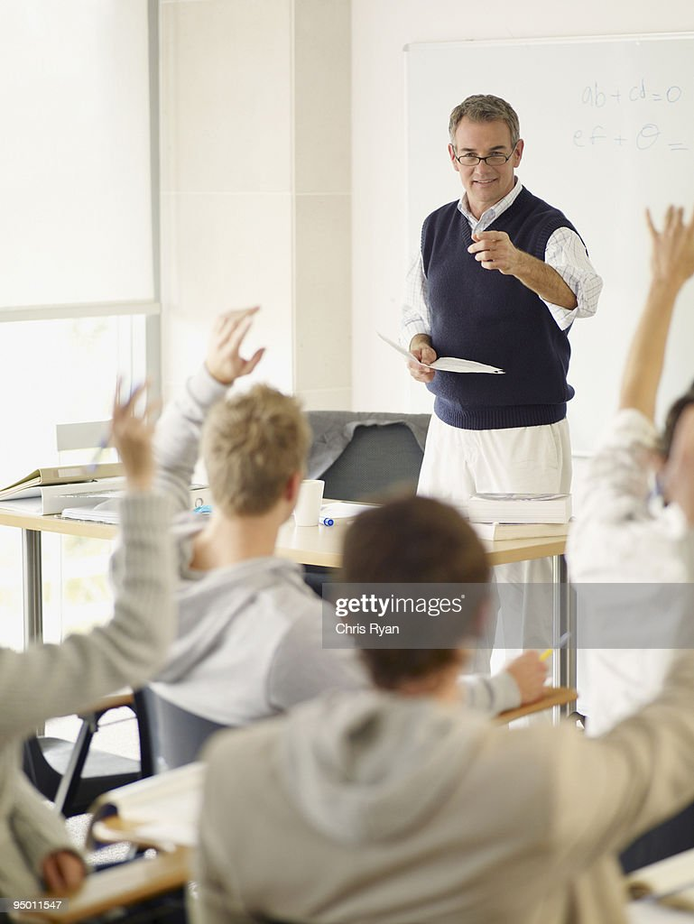 Professor pointing at college students with hands raised in classroom : Stock Photo