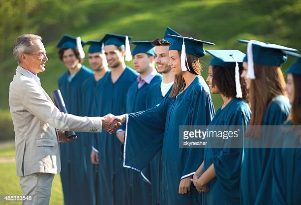 Professor shaking hands with graduation student outdoors.