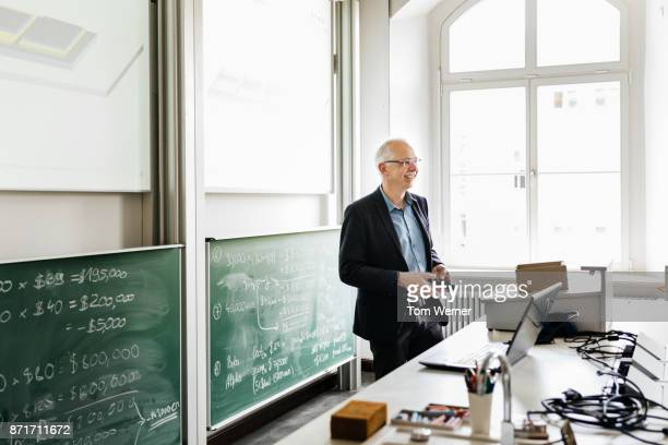 professor standing at his desk in lecture hall smiling - professor stock pictures, royalty-free photos & images