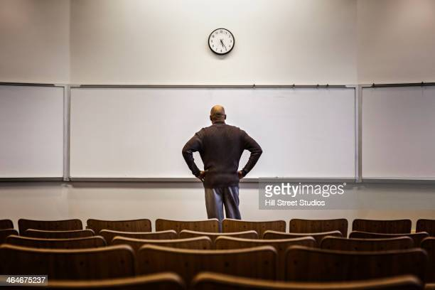 professor standing in empty classroom - lecturer stock pictures, royalty-free photos & images