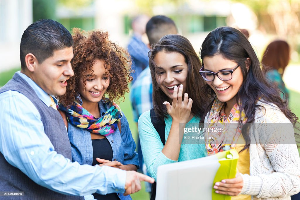 Professor talking to diverse group of high school girls : Stock Photo