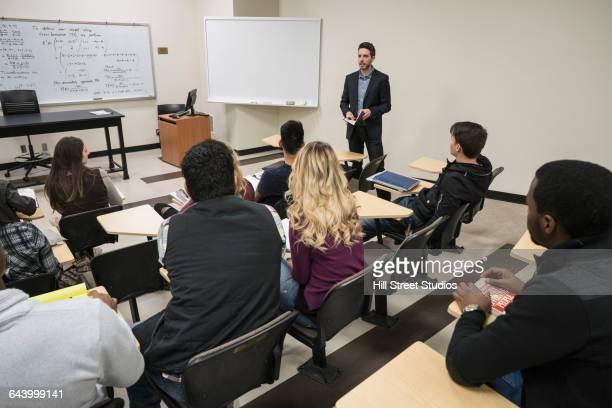professor talking to students in college classroom - caldwell idaho foto e immagini stock