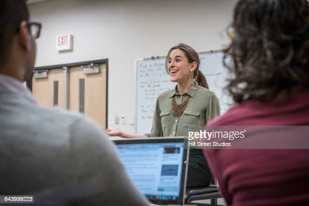 professor talking to students in college classroom - college professor stock photos and pictures
