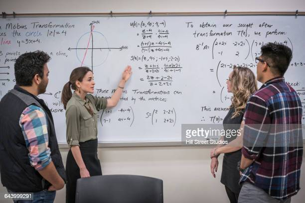 Professor talking to students in college classroom