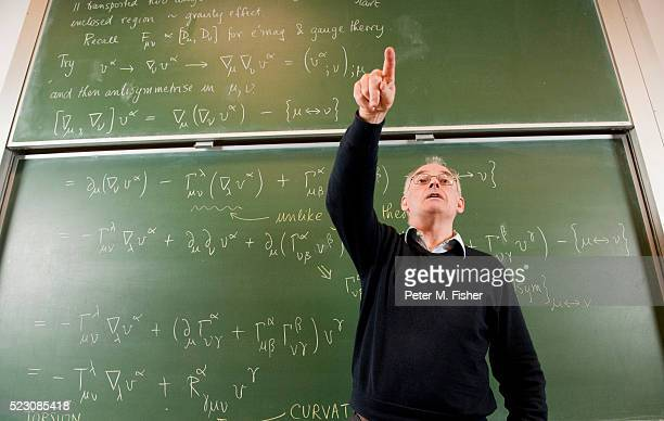 professor teaching in front of blackboard - physicist stock pictures, royalty-free photos & images