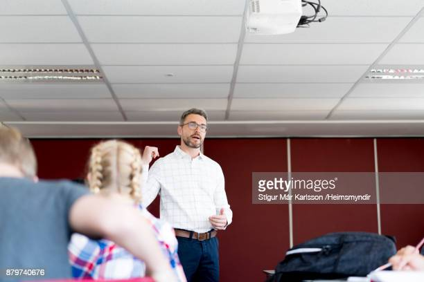professor teaching to teenage students at school - differential focus stock pictures, royalty-free photos & images