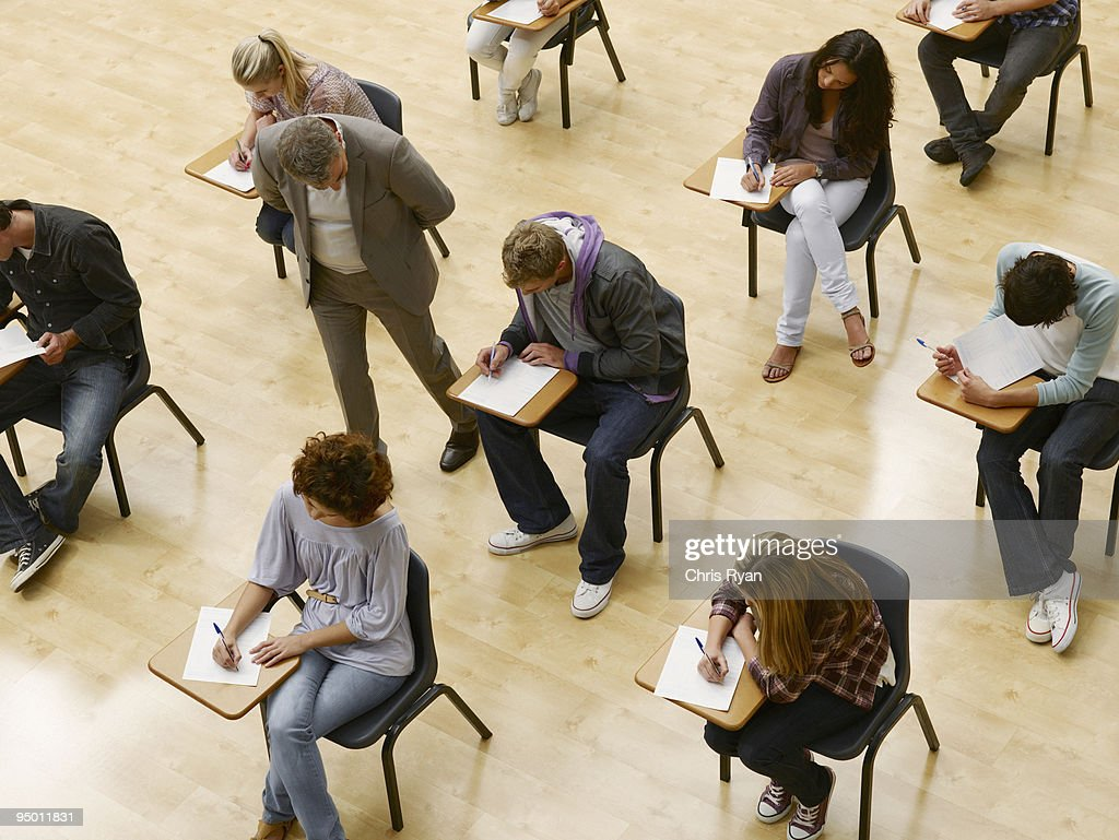 Professor walking by college students taking test in classroom : Stock Photo