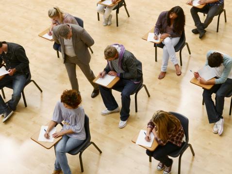 Professor walking by college students taking test in classroom - gettyimageskorea