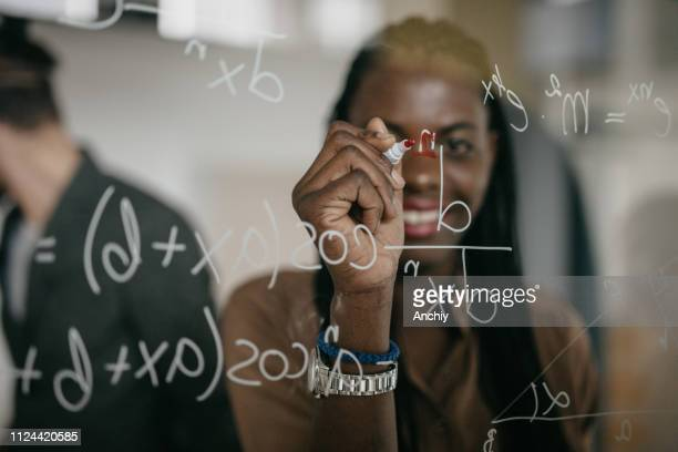 professor writing mathematical formulas on a glass - formula stock pictures, royalty-free photos & images