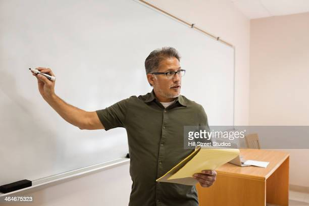 Professor writing on whiteboard in classroom