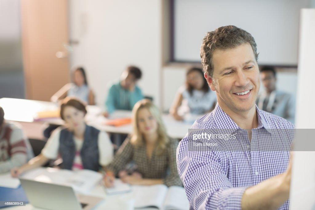 Professor writing on whiteboard in classroom : Stock Photo