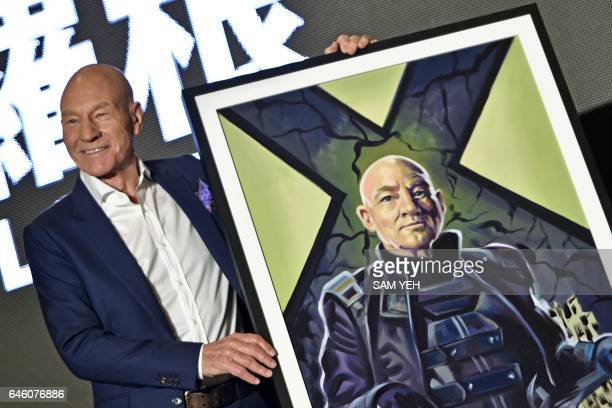 'Professor X' in the XMen series' Patrick Stewart poses for photos with a gift of a painting during a press conference for the film 'Logan' in Taipei...