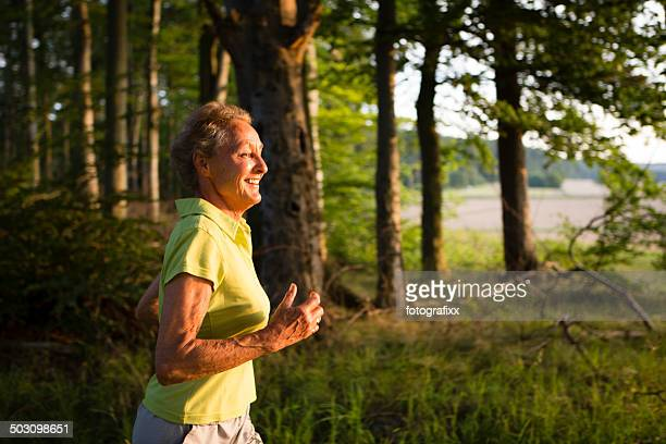 profil senior woman jogging through the forest