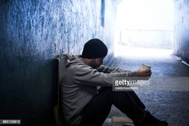 profile close up view of young homeless caucasian male sitting and begging in dark subway tunnel - homeless foto e immagini stock