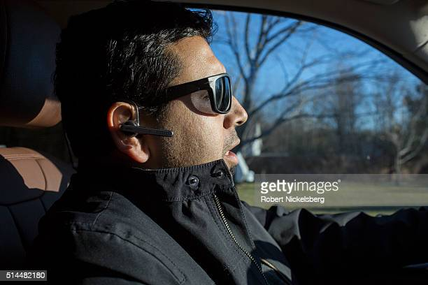 Profile closeup of Central Market owner Somu Timsina as he talks on a bluetooth headset and makes a delivery in his car Winooski Vermont February 2...