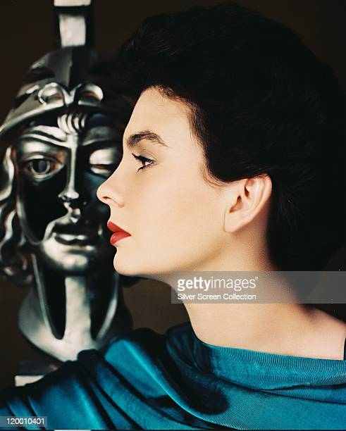 Profile headshot of Jean Simmons Britiish actress posing beside a bust in a studio portrait against a black background circa 1960