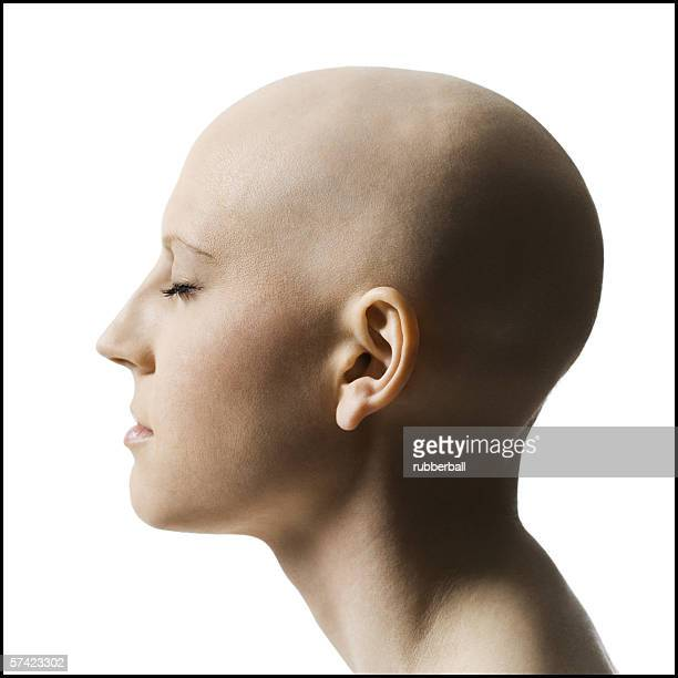 profile of a bald young woman with her eyes closed - bald woman stock photos and pictures