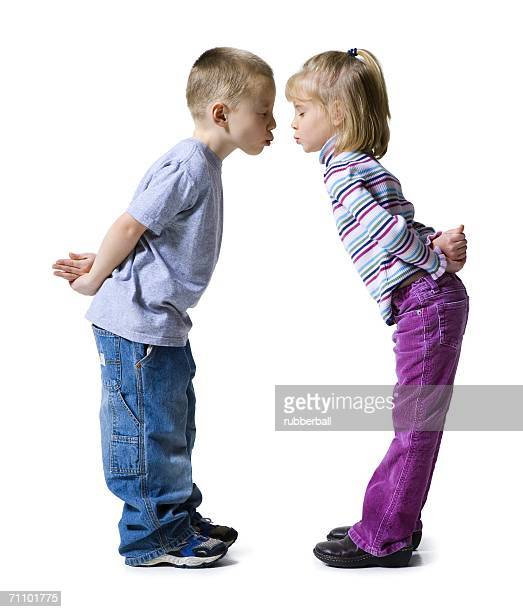 Profile of a boy and a girl almost kissing each other with their hands behind their backs