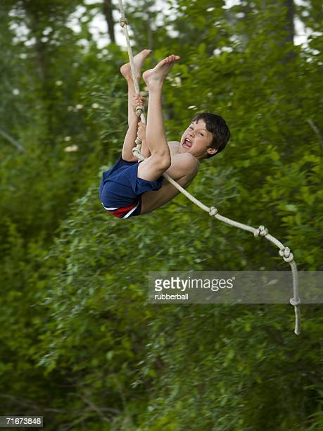 Profile of a boy swinging on a rope