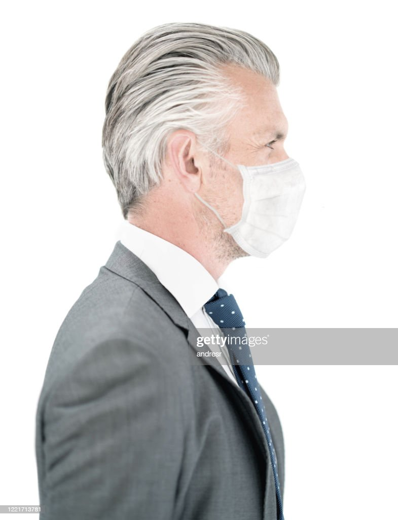 Profile of a business man wearing a facemask to avoid COVID-19 : Stock Photo