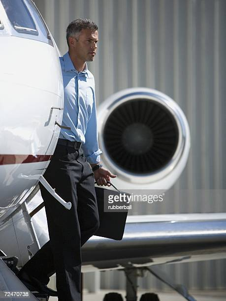 Profile of a businessman stepping down from an airplane