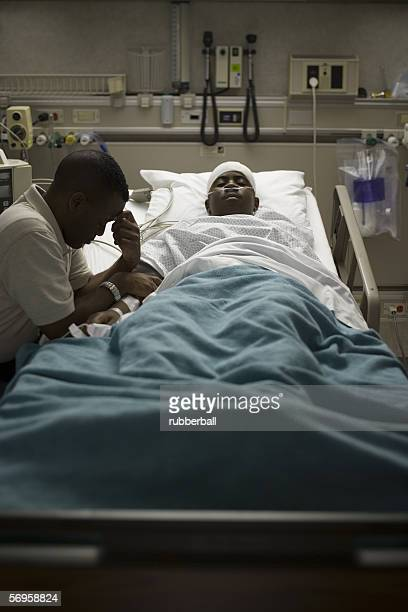 Profile of a father sitting beside his son lying on the bed