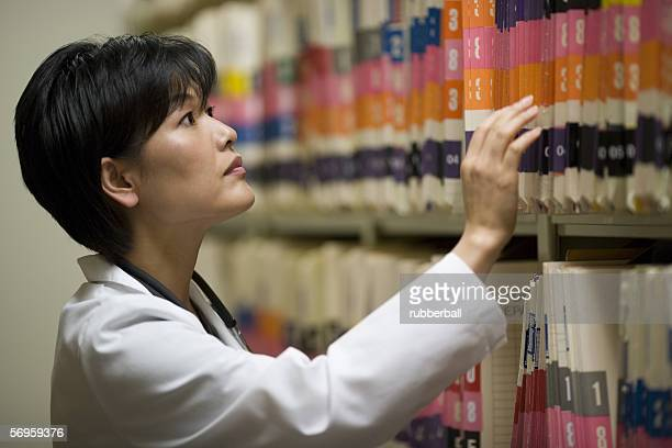 Profile of a female doctor looking for a file in the medical records room