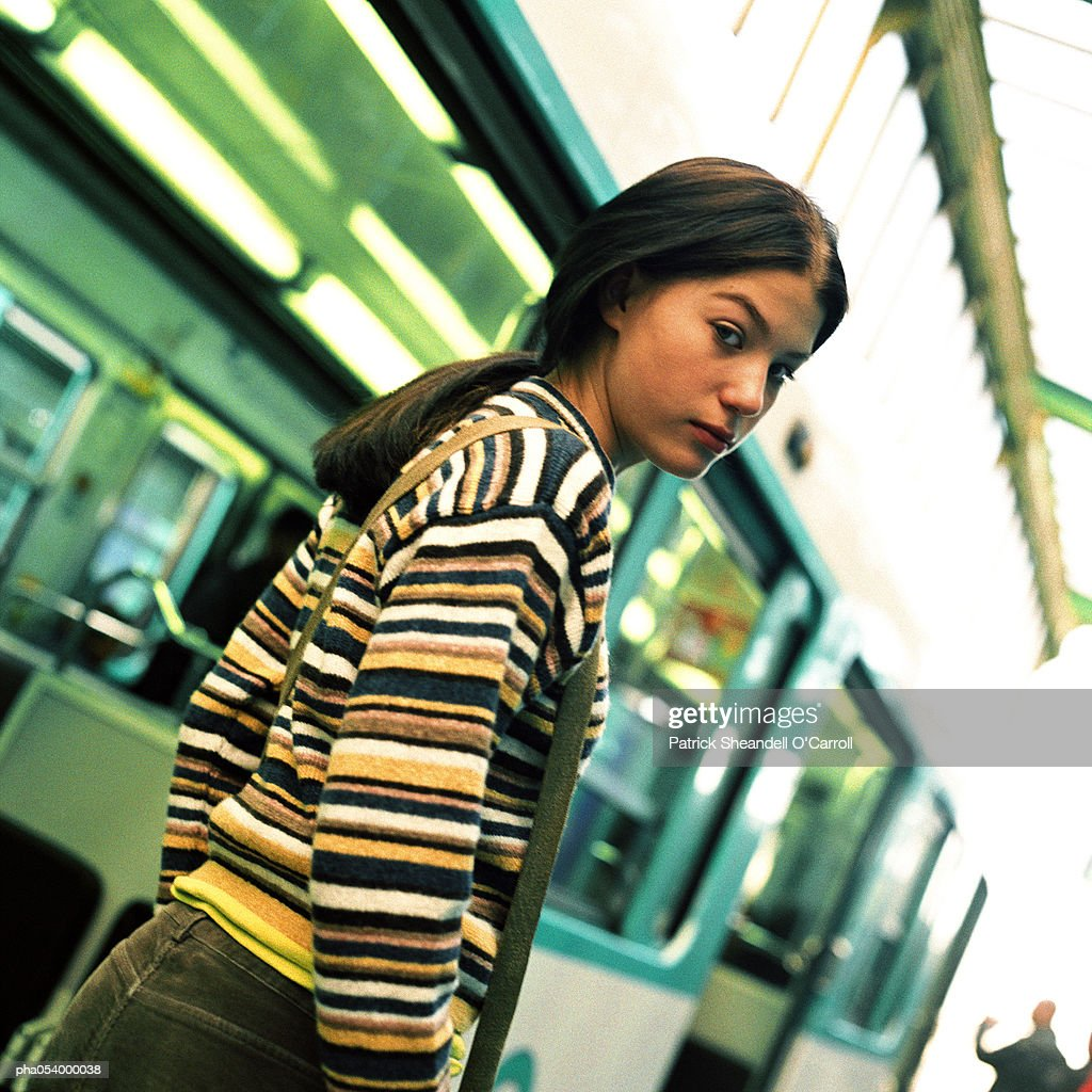 Profile of a female teenager standing next to a subway train : Stockfoto