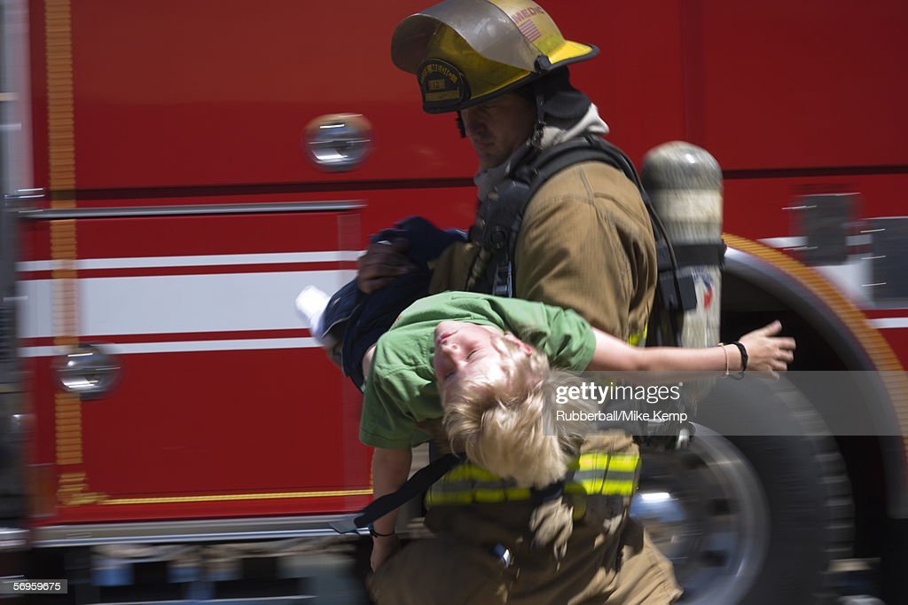 Profile of a firefighter carrying a boy : Stock Photo