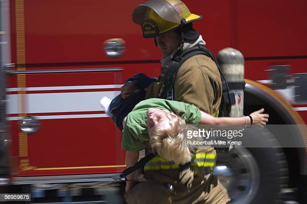 Profile of a firefighter carrying a boy