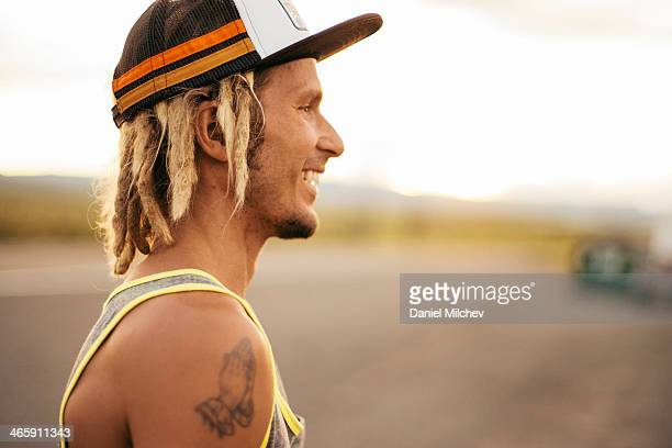 Profile of a guy with dreadlocks and tattoo.