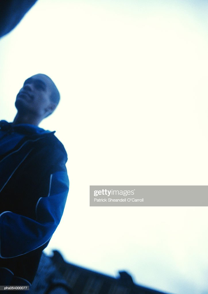 Profile of a male teenager in blue, blurred : Stock Photo