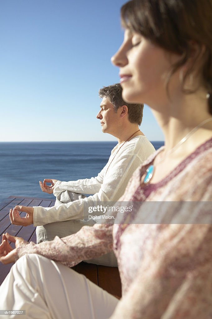 Profile of a Man and Woman Sitting on Decking by the Sea, Meditating in the Lotus Position : Stock Photo