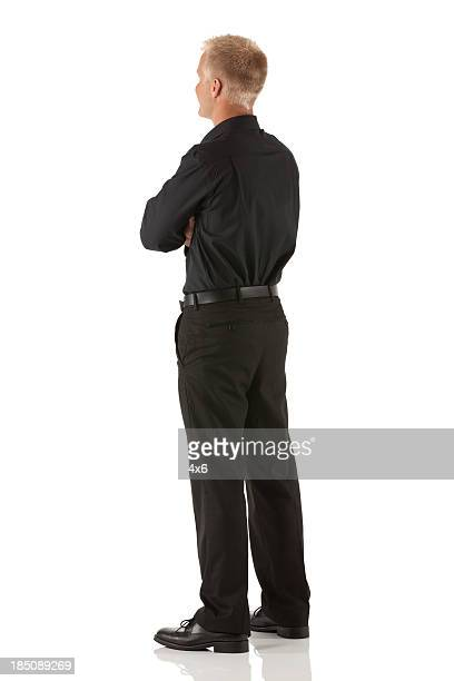 profile of a man standing with his arms crossed - black trousers stock pictures, royalty-free photos & images