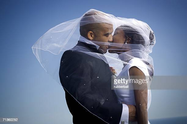 Profile of a newlywed couple kissing each other