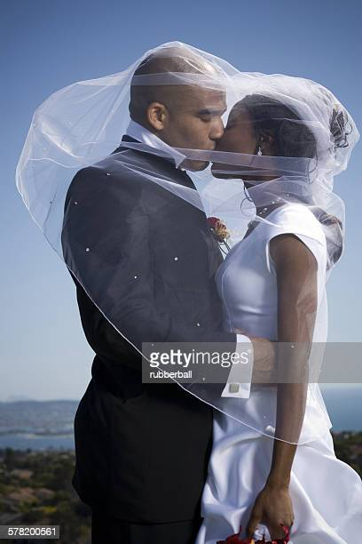 Profile of a newlywed couple kissing each other under a veil