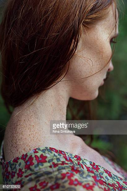 Profile of a red young woman with freckles
