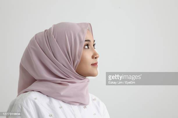 profile of a smiling young woman hijab over white background - 宗教的なベール ストックフォトと画像