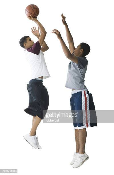 Profile of a teenage boy and a young man playing basketball
