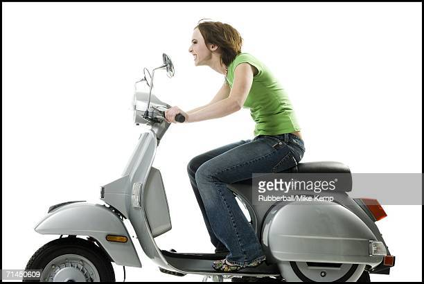 Profile of a teenage girl riding a scooter