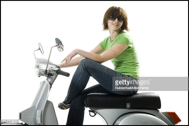 Profile of a teenage girl sitting on a scooter