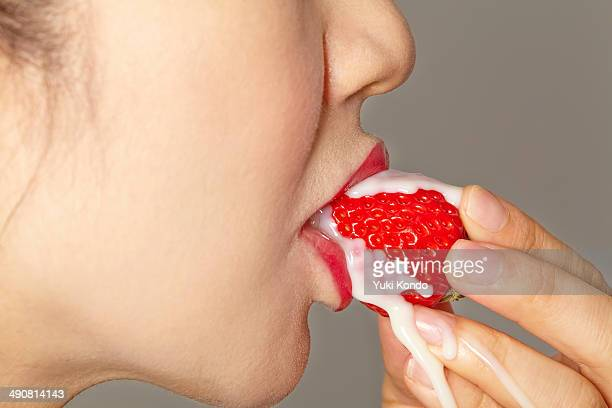 Profile of a woman eating a strawberry.