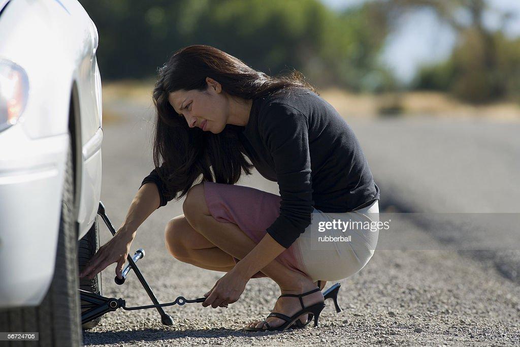 Profile of a woman fixing a flat tire : Photo