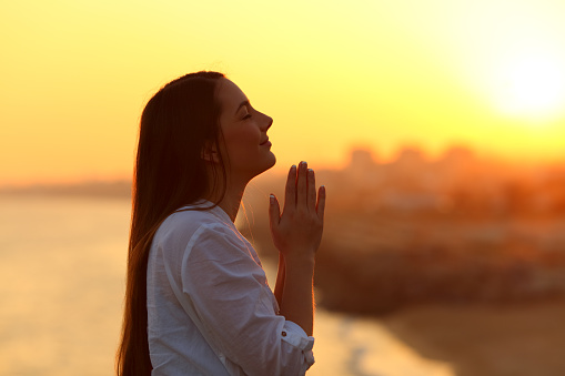 Profile of a woman praying at sunset 915213254