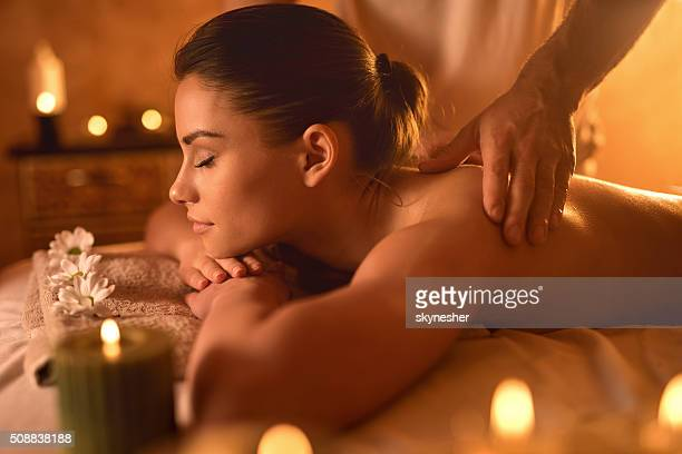 Profile of a woman receiving back massage at spa.