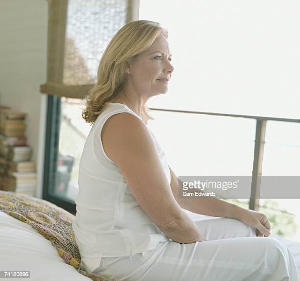 profile of a woman sitting in bedroom - alleen één oudere vrouw stockfoto's en -beelden