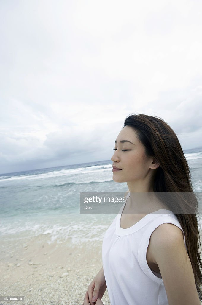 Profile of a Woman Standing on a Beach With Her Eyes Closed : Stock Photo