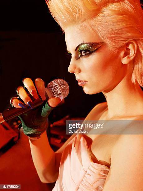 profile of a young female punk singer with exaggerated eye make-up and a blonde quiff holding a microphone - 指なし手袋 ストックフォトと画像